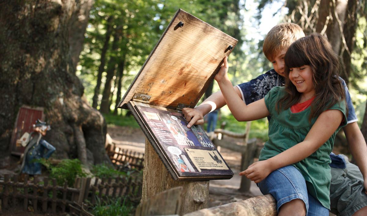 Sie klappt eine Holztafel auf und liest