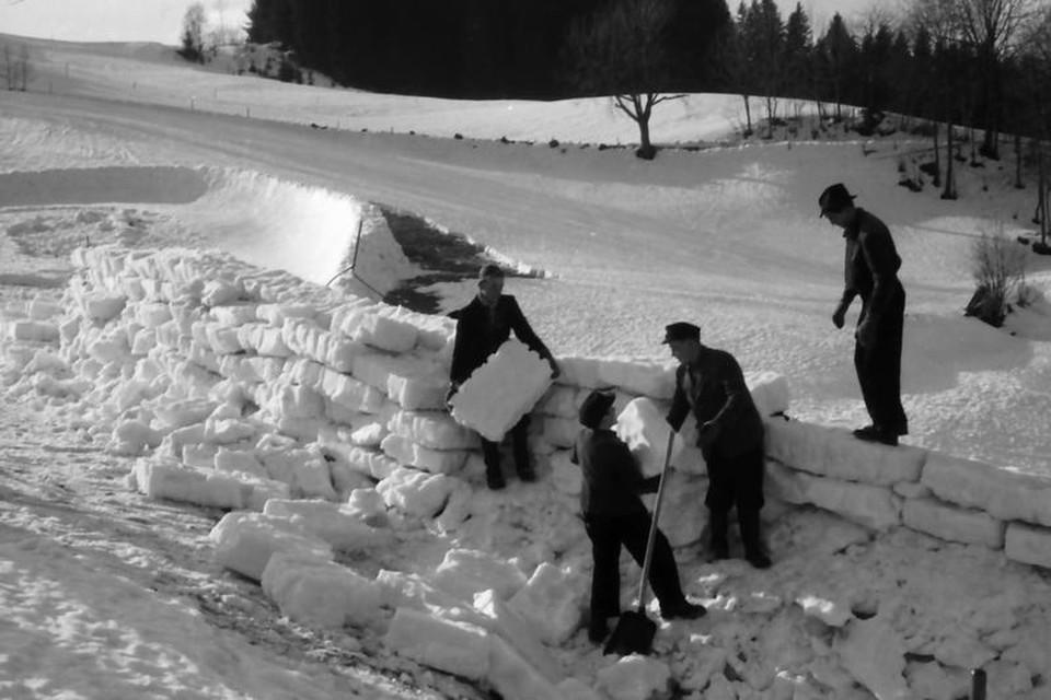 Für die Steilwände der Bobbahn werden Schneeblöcke zurechtgeschnitten und wie bei einem Iglu aufeinander geschichtet.