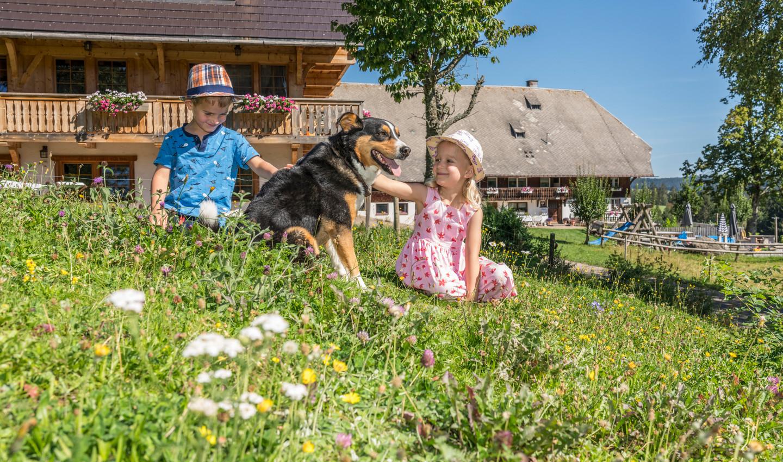Kinder sitzen vor dem Haus und genießen die Zeit mit dem Hund