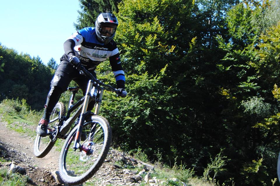 Mountainbikeneuling nimmt Tempo auf und springt über Hügelchen und überwindet kleine Felsvorsprünge.