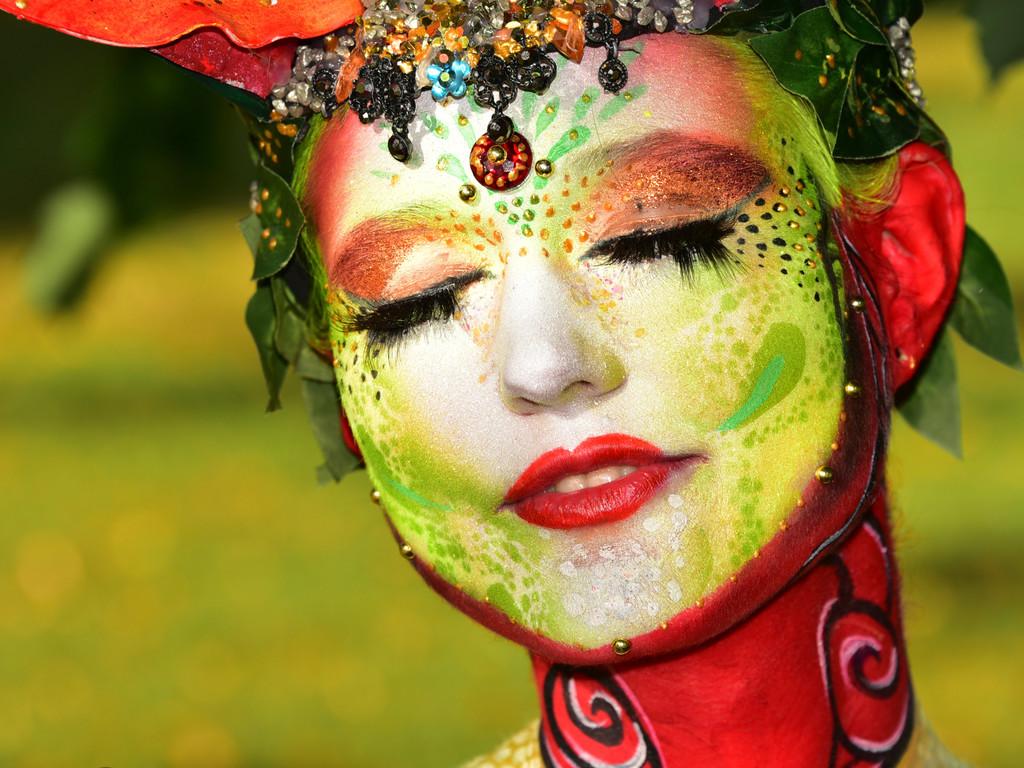 In rot, grün, blau und orange erstrahlt die Kunst der Bodypainting Künstler und Künstlerinnen.