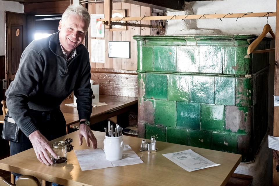 Mit dem urigen Kachelofen heizt Hüttenwirt Ernst Hug die gemütliche Stube ein.