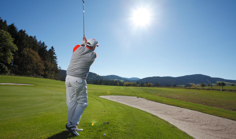 Mann spielt bei strahlendem Sonnenschein Golf