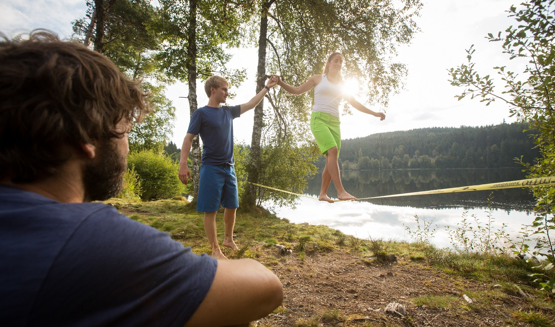 Personen mit einer Slackline am See