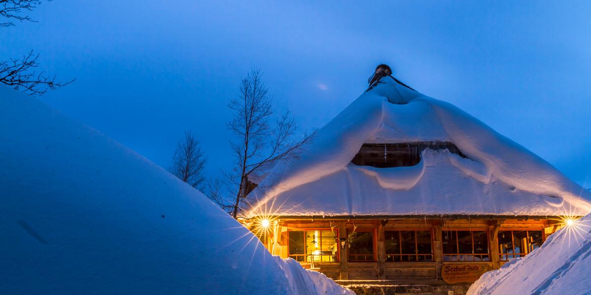 Zwischen den hohen Schneehügeln sieht die Hütte aus wie ein gestrandetes Holzschiff.