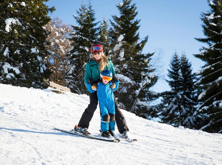 Mutter und Kind fahren gemeinsam einen verschneiten Berg hinunter