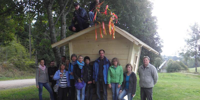 Nach einem kurzen Halt und einem Erinnerungsfoto mit der Gruppe an der neu errichteten Spielhütte geht es weiter.