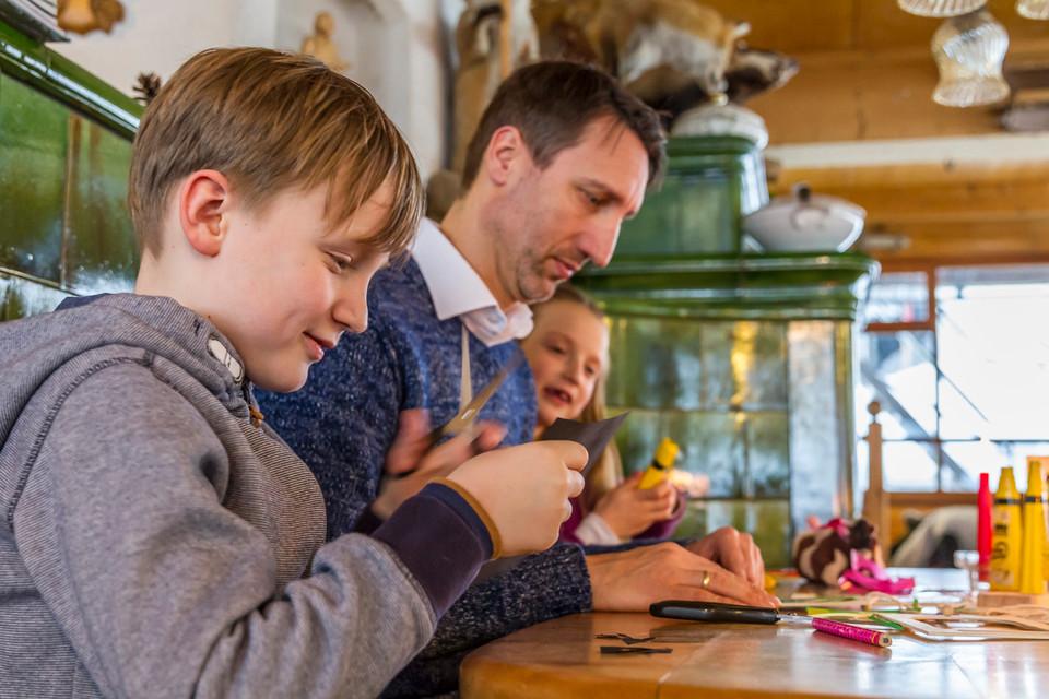 Emsige Kinderhände greifen nach den Holz-Rohlingen, die Patrick auf dem Tisch verteilt hat.