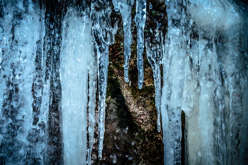Breite Eiszapfen hängen wie Gletscherzungen von den schroffen Felsen herab.