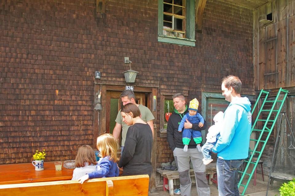 An der Haustür des 300 Jahre alten Hauses mit den dunklen Holzschindeln hängt als Klingel eine eiserne Glocke, die ein kleiner Hahn ziert.