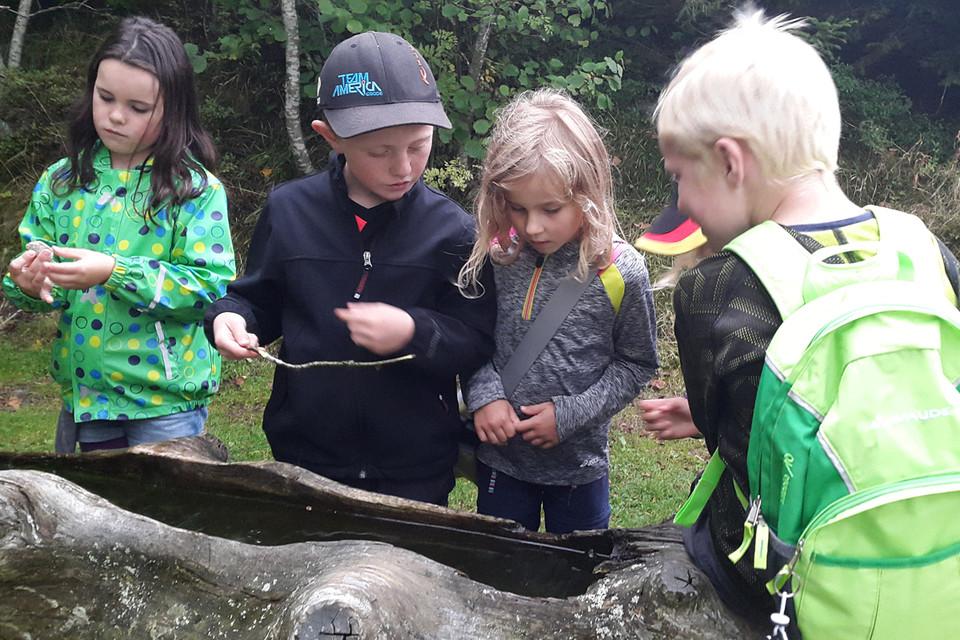 """Aus einem Brunnen fischen die Kinder kurz darauf Algen, die sich laut Jonah """"cool"""" anfühlen."""