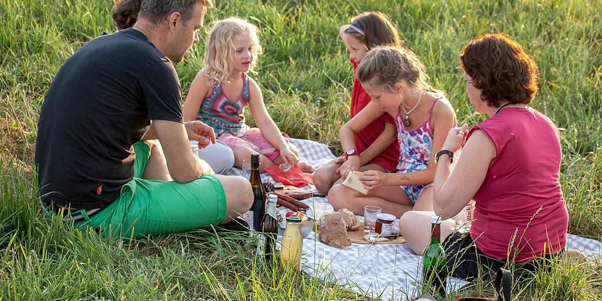 Jetzt sitzen wir mit Kindern und Freunden auf einer karierten Picknickdecke im hohen Gras, auf der vor lauter Leckereien fast kein Platz mehr zum Sitzen ist.