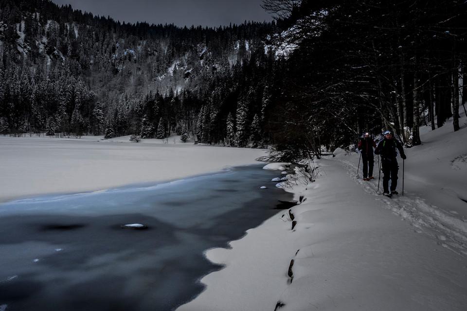 Der See ist komplett zugefroren, nur an einer Uferseite schimmert das Wasser türkisblau durch die hauchdünne Eisschicht.