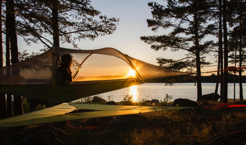 Person im Baumzelt bei Sonnenuntergang