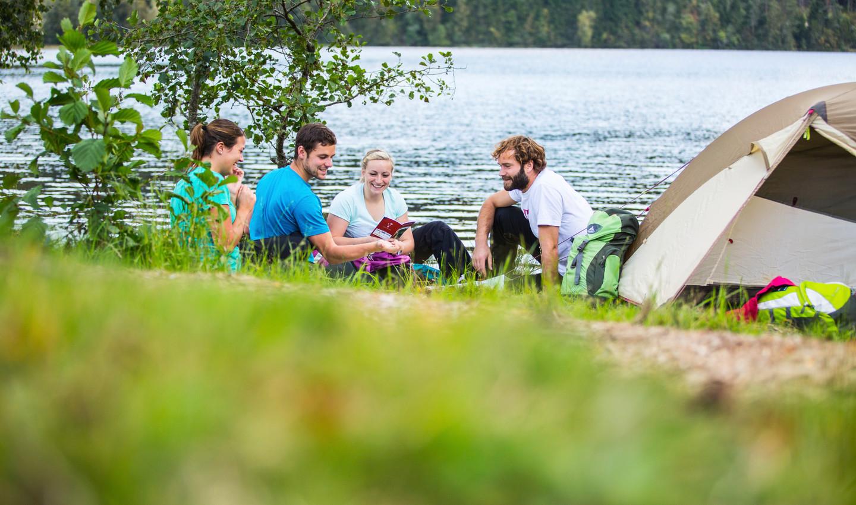 Personen sitzen gemeinsam am Ufer mit ihrem Zelt