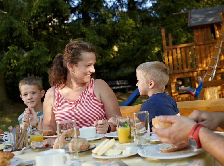 Familie beim gemeinsamen Frühstücken im Freien